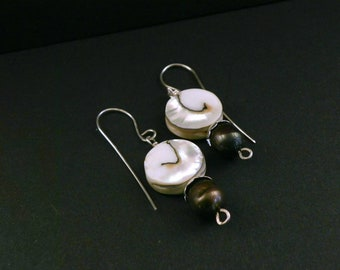Sterling silver hand forged dangle earrings with swirling round mother of pearl composit beads.