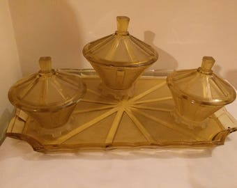 A stunning Art Deco dressing table set with three lidded pots on a glass tray in frosted amber glass.