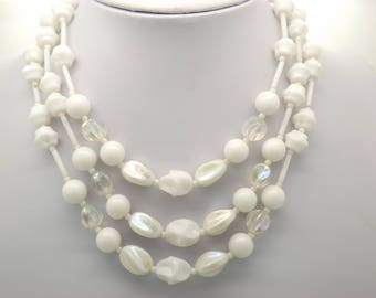 A lovey chunky retro period 1950s / 60s triple row vintage jewelry necklace made of shiny mixed size and shape clear and white plastic beads