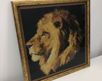 Lion embroidered picture with a cross stitch artwork King of beasts from a series of graphics in brownyellow tones on a black background