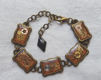 Retro/steampunk resin inclusion, wheels of watches amid pink