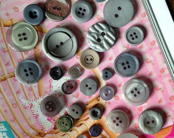 Set of 32 beautiful grey buttons of varying sizes.