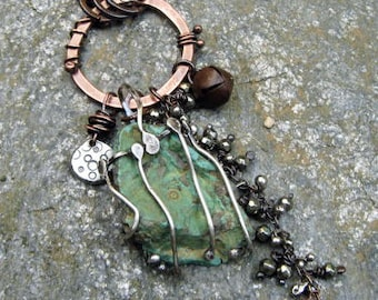 Large rough turquoise stone caged in sterling silver with rusty bell, pyrite and silver dangle