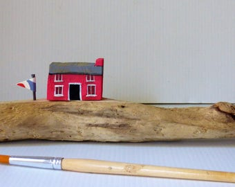 Driftwood ridge with pink cottage
