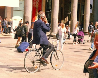 Bicycling businessman photobombed, color photograph