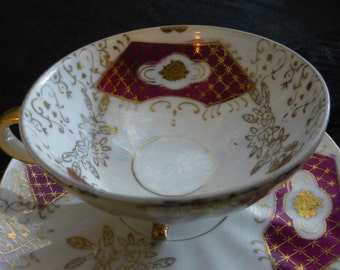 Japanese Mother of Pearl White Luster Ware Three Footed Teacup and Saucer with Magenta Cartouches, Gold Roses, and Intricate Gold Decoration