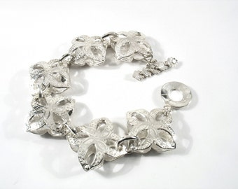 3D engraved  sterling silver flowers,nice weight , fits almost all thanks to the extra  chain. The bracelet that will make other jealous.