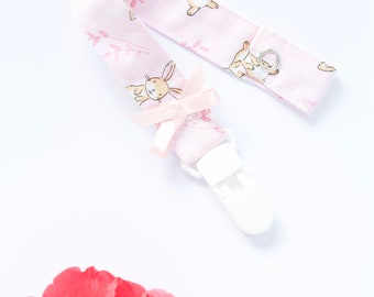 pink with little bunnies dummy clip/ pacifier clip featuring a pink satin bow