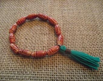 Patterned wood bead bracelet with teal tassel