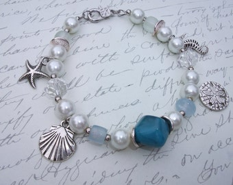 Pearl bracelet with starfish seahorse shell and sand dollar silver charms