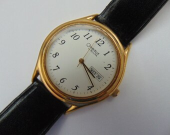 Caravelle by Bulova gold tone bezel, stainless, day/date quartz watch