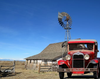 Antique 1930's Ford model A sedan and vintage farm buildings and windmill in the background.