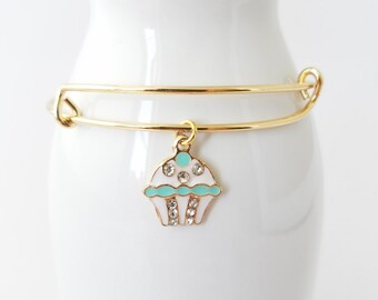 Cupcake in aqua and white with rhinestones on a gold plated bangle bracelet.