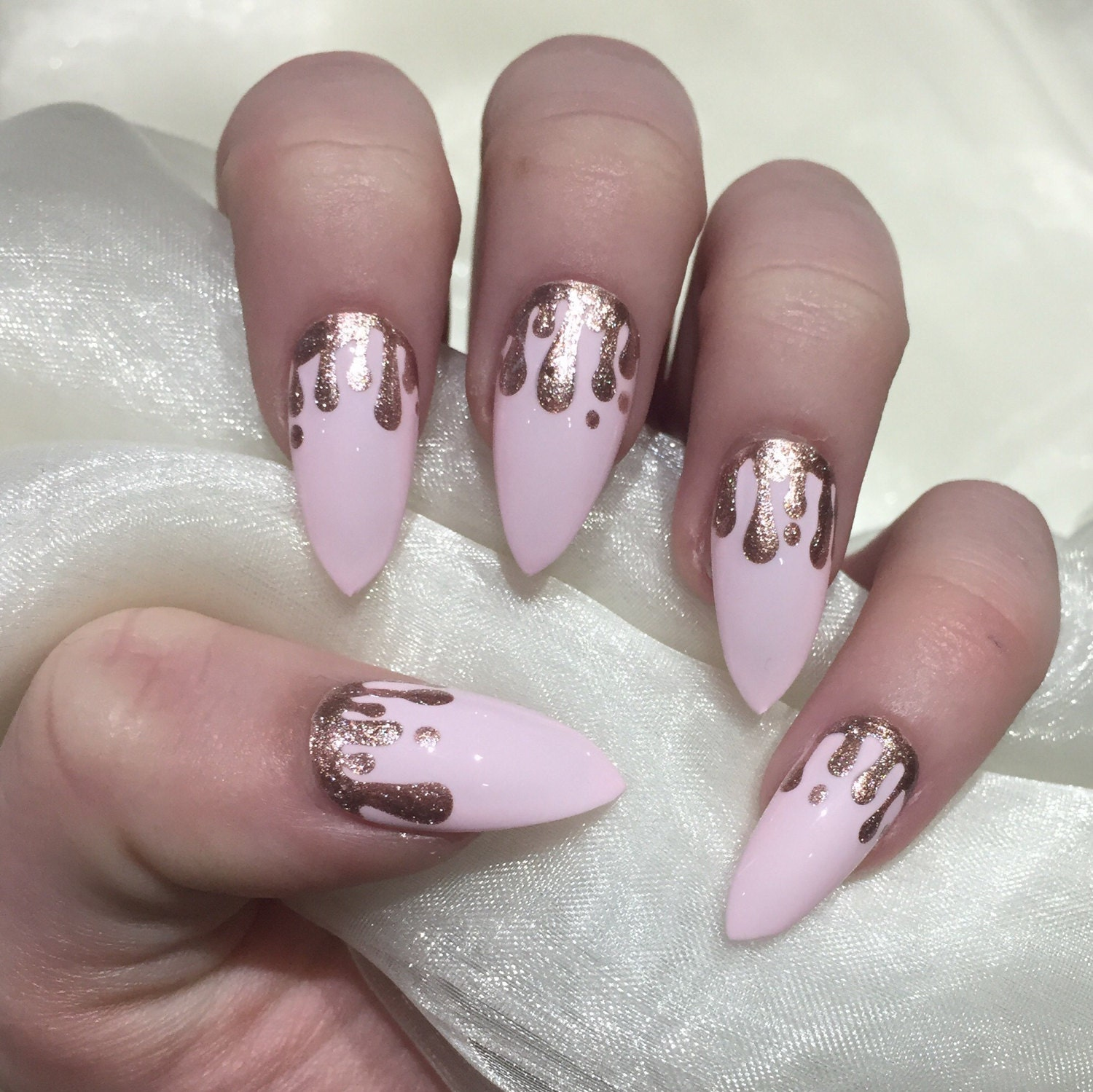 Baby pink stiletto false nails with rose gold glitter drip