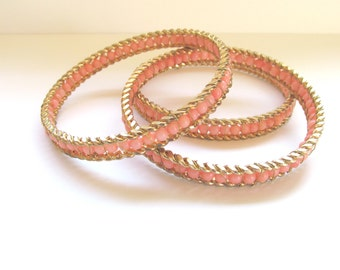 Faux coral pink bead gold tone wire bangles
