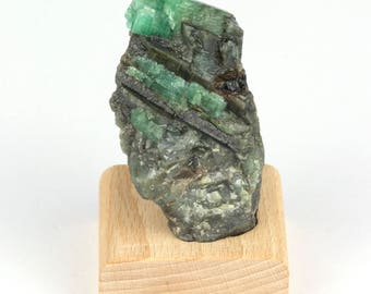 Rough emerald on base of beech wood of 101 grams.