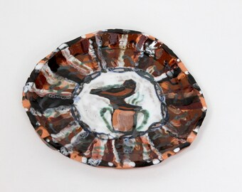 Earthenware plate of bird and steaming cauldron