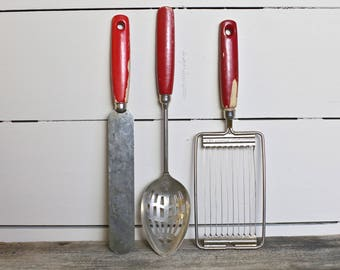 Old cooking utensils With red wood handles