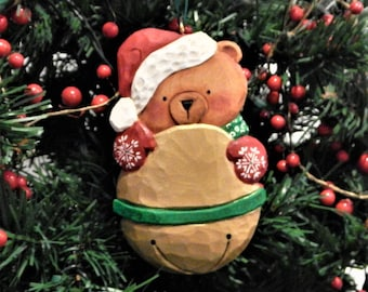Hand Carved Beary Merry Christmas Ornament holds a gold bell, woodburned and hand painted for a gift, a legacy of love for years to come.