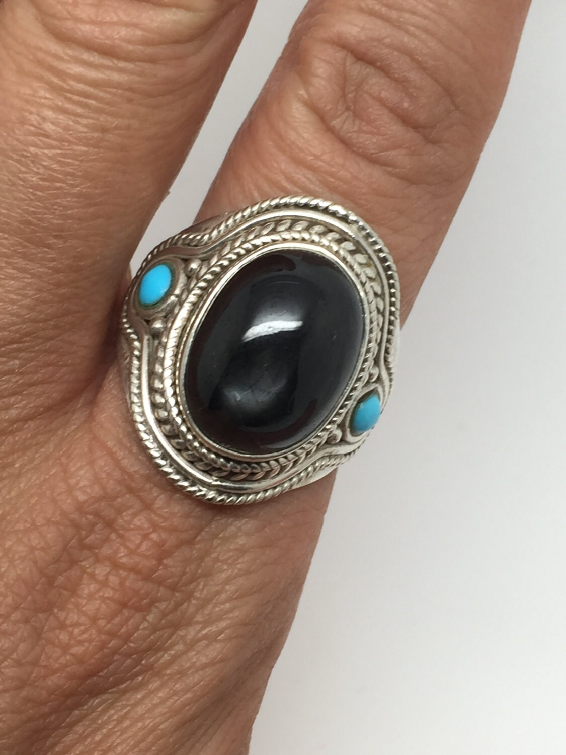 silver ring with black star stone and two small turquoise on