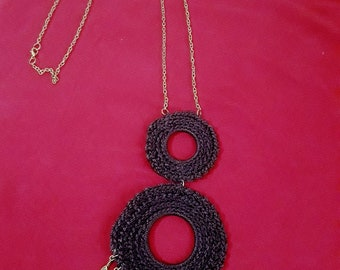 Necklace with two woven spheres, black color.