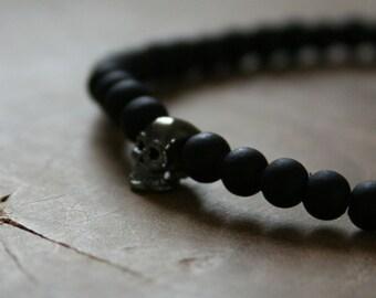 Black Skull: an elastic beaded bracelet with gunmetal skull and matte black glass beads.