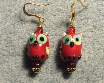 Red lampwork owl bead earrings adorned with red Czech glass beads.