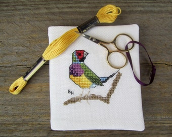 Cross stitch needlebook on very pale mint-coloured evenweave and red fabric lining - Gouldian Finch.