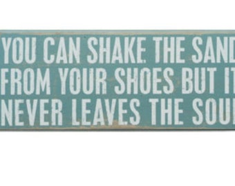 You can shake the sand from your shoes but it never leaves your soul Wooden Sign