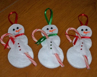 Sparkly white felt snowman candy cane holder.
