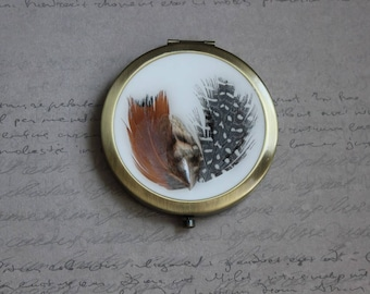 Mirror round pocket, covered with resin, bronze appearance and 3 feathers