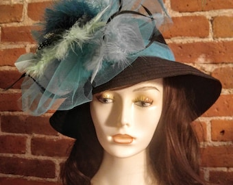 Black small brimmed hat with turquoise feather accents!