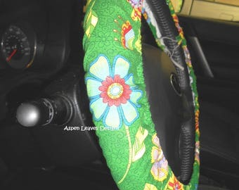 Daisy steering wheel cover. Large yellow and white floral. Lined cover. Seat belt covers and key fob options. Purple and blue daisies.