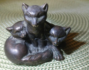 Three Cast Metal Foxes Huddling Together