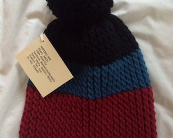 Black, blue, red knit hat with pom-pom