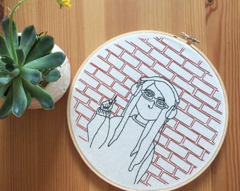 Girl with headphones against brick wall, Black linework, Hand embroidered wall art