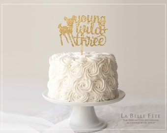 YOUNG, WILD + THREE gold glitter cake topper with baby deer / fawn