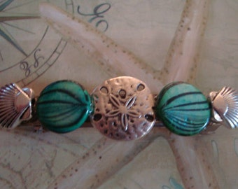 Beautiful multi-shells barrette is made with a silver metal sand dollar and scallop shells, teal dyed, stamped shell beads. 2 3/4 inch clip.