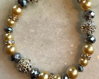 "Cream-colored acrylic pearl beads, metal capped beads, mirrored beads and smoky crystal beads in this 7"" stretch bracelet"