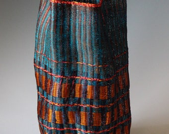 A loom woven copper vessel