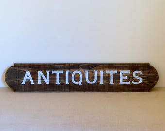 "Wooden cut and patinated with the word ""Antiques"" sign painted in white"