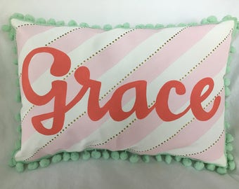 Baby pillow in pink stripes with tiny gold polka dots and name in coral