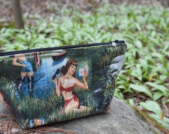 Zippered makeup bag in a retro pinup fabric with clear vinyl top layer