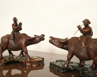 Vintage Chinese figures sat on water buffalo