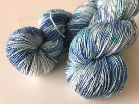 Hand dyed super-wash Merino sock yarn with nylon and a string of silver polyamide. Dyed in shades of blue