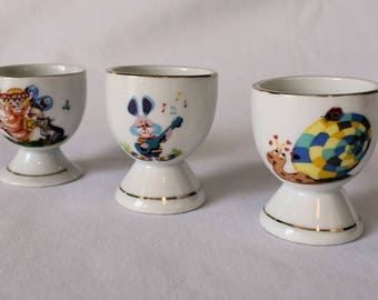 Set of Vintage Egg Cups with Snail, Fairy, and Rabbit Designs