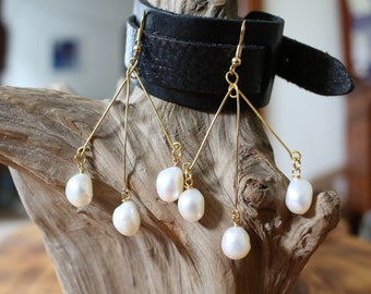 The pendulum, all freshwater pearls gold plated ware, the middle swings to and fro.