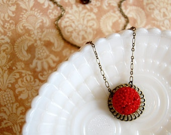 Red glass vintage floral cabochon on sun inspired filigree hung on fancy aged brass chain- Rising Sun.
