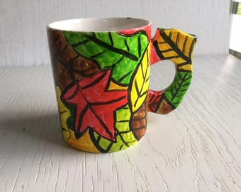 18 - Leafy mug with green brown red yellow leaves