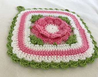 Square Kitchen pot holder with central pink flower made of cotton crochet. Kitchen accessory, decoration, gift idea.